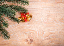 Gold Christmas bells and fir tree branch on a rustic wooden background. Xmas card. Happy New Year. Top view with copy space Stock Photos