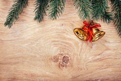 Gold Christmas bells and fir tree branch on a rustic wooden background. Xmas card. Happy New Year. Top view with copy space Royalty Free Stock Photography