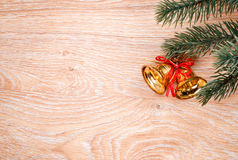 Gold Christmas bells and fir tree branch on a rustic wooden background. Xmas card. Happy New Year. Top view Royalty Free Stock Image