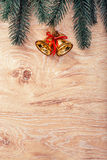Gold Christmas bells and fir tree branch on a rustic wooden background. Xmas card. Happy New Year. Top view Stock Photography