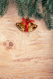 Gold Christmas bells and fir tree branch on a rustic wooden background. Xmas card. Happy New Year Stock Photos