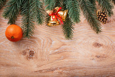 Gold Christmas bells and fir tree branch on a rustic wooden background. Xmas card. Happy New Year Stock Images