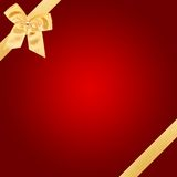 Gold Christmas bow on red card Royalty Free Stock Image