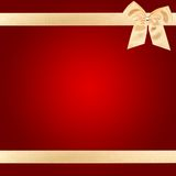 Gold Christmas bow on red card. Gold Christmas bow on square red card Royalty Free Stock Photo