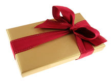 Gold Christmas Box. A Christmas present wrapped in gold paper with red ribbon Royalty Free Stock Photos