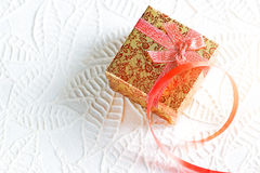 Gold christmas box tied in ribbon on white paper texture Stock Photography