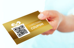 Gold christmas coupon holded by hand over white. Background. focus on coupon Stock Images