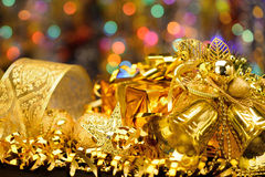 Gold Christmas decorations. Boxes, ribbons, stars, bells on the bokeh background Royalty Free Stock Photo