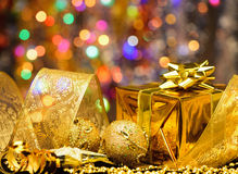 Gold Christmas decorations. Boxes, ribbons, stars, bells on the bokeh background Royalty Free Stock Photos
