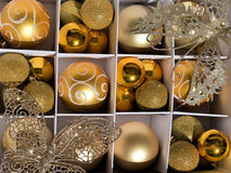 Gold christmas decorations. Box of gold Christmas baubles and butterflies Stock Images
