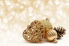 Gold christmas decorations. On glitter sparkle background Stock Image