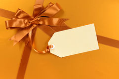 Gold christmas gift background ribbon bow, gift tag or manila label Stock Photography