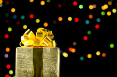 Gold christmas gift box with ribbon and bow on bokeh lights background Royalty Free Stock Photography