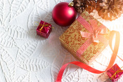 Gold christmas gift box tied in ribbon with red bauble on white paper texture Stock Images