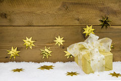 Gold christmas gift on snow and gold stars on wooden background. Stock Photo
