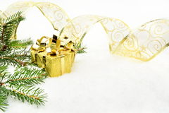 Gold christmas gifts with gold ribbon and needles fir on snow. Decoration of gold christmas gifts, gold ribbon on snow christmas tree branch on white Stock Image