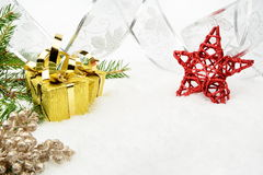 Gold christmas gifts with silver ribbon and needles fir with red. Decoration of gold christmas gifts, silver ribbon on snow with red star, christmas tree branch Stock Photos
