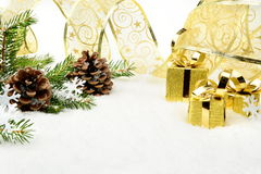 Gold christmas gifts,snowflakes with gold ribbon and needles fir Royalty Free Stock Photography