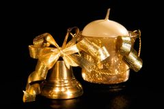 Gold christmas handbell and candle. Before a holiday Royalty Free Stock Images