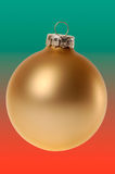 Gold Christmas ornament / bauble on red and green stock photos