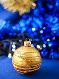 Gold Christmas ornament on blue holiday background. Xmas and New Year card Stock Images