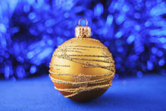 Gold Christmas ornament on blue holiday background. Xmas and New Year Royalty Free Stock Photos