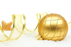 Gold Christmas ornament and ribbon in snow Stock Photo
