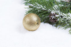 Gold Christmas Ornament on Snow with Fir Branch Royalty Free Stock Photos