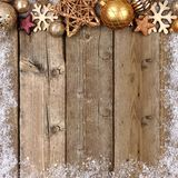 Gold Christmas ornament top border with snow frame on wood Stock Photo