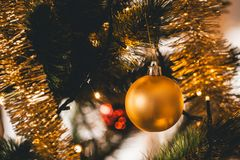 Gold Christmas Ornaments and decoration on a Christmas tree. Christmas Ornaments and decoration on a Christmas tree, green tree inside house with the lights on Stock Photos