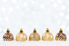 Gold Christmas ornaments in snow with twinkling background Stock Image
