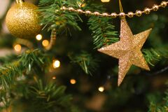 Gold Christmas ornaments on tree Stock Photos