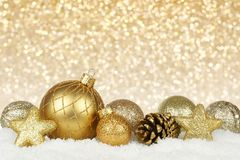 Gold Christmas ornaments with twinkling background. Gold Christmas ornament border in snow with twinkling gold light background Stock Photo