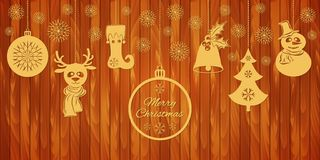 Gold Christmas pendants a bell with holly, ball, fir-tree with snowflakes, a deer in scarf, stocking. A border isolated on wooden Royalty Free Stock Photo