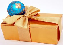 Gold Christmas present. Gold christmas box and blue ball royalty free stock photo