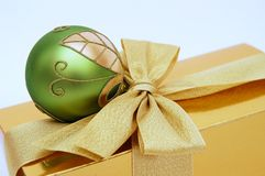 Gold Christmas present. Gold christmas box and green ball royalty free stock images