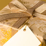 Gold Christmas present with blank tag wishing card Royalty Free Stock Image