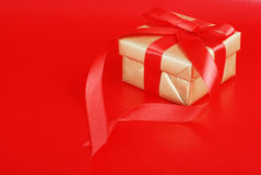 Gold christmas present on red. Closeup of a Gold christmas present on red with bow Stock Photos