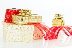 Gold Christmas Presents. With ribbon reel and bows on white background Stock Photos