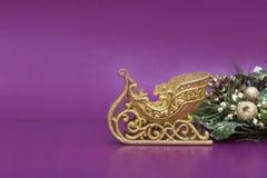 Gold Christmas sledge on purple Stock Photo