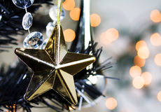 Gold christmas star. A gold star on a black christmas tree Royalty Free Stock Images
