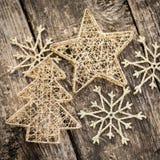 Gold Christmas tree decorations on grunge wood Stock Photos