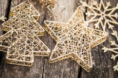 Gold Christmas tree decorations on grunge wood. Background. Winter holidays concept. Shallow depth of fields Stock Image