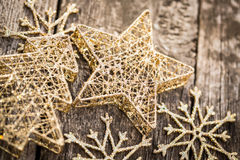 Gold Christmas tree decorations on grunge wood. Background. Winter holidays concept. Shallow depth of fields Stock Photo