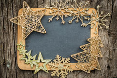 Gold Christmas tree decorations on vintage wooden blackboard Stock Image