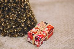 Gold christmas tree and a present Stock Images