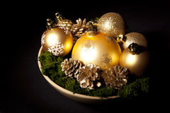 Gold christms glass balls with pinecones over dark Stock Photo