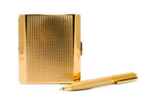 Gold cigarette-case with a gold pen Royalty Free Stock Photos