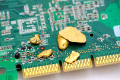 Gold And Circuitry. Gold is an important part of modern technology. raw gold nuggets on top of a finished circuit board  with gold plated connections Royalty Free Stock Images