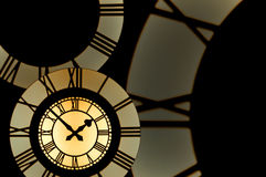 Gold clockface surrounded by parts of roman numeral clockfaces royalty free stock image
